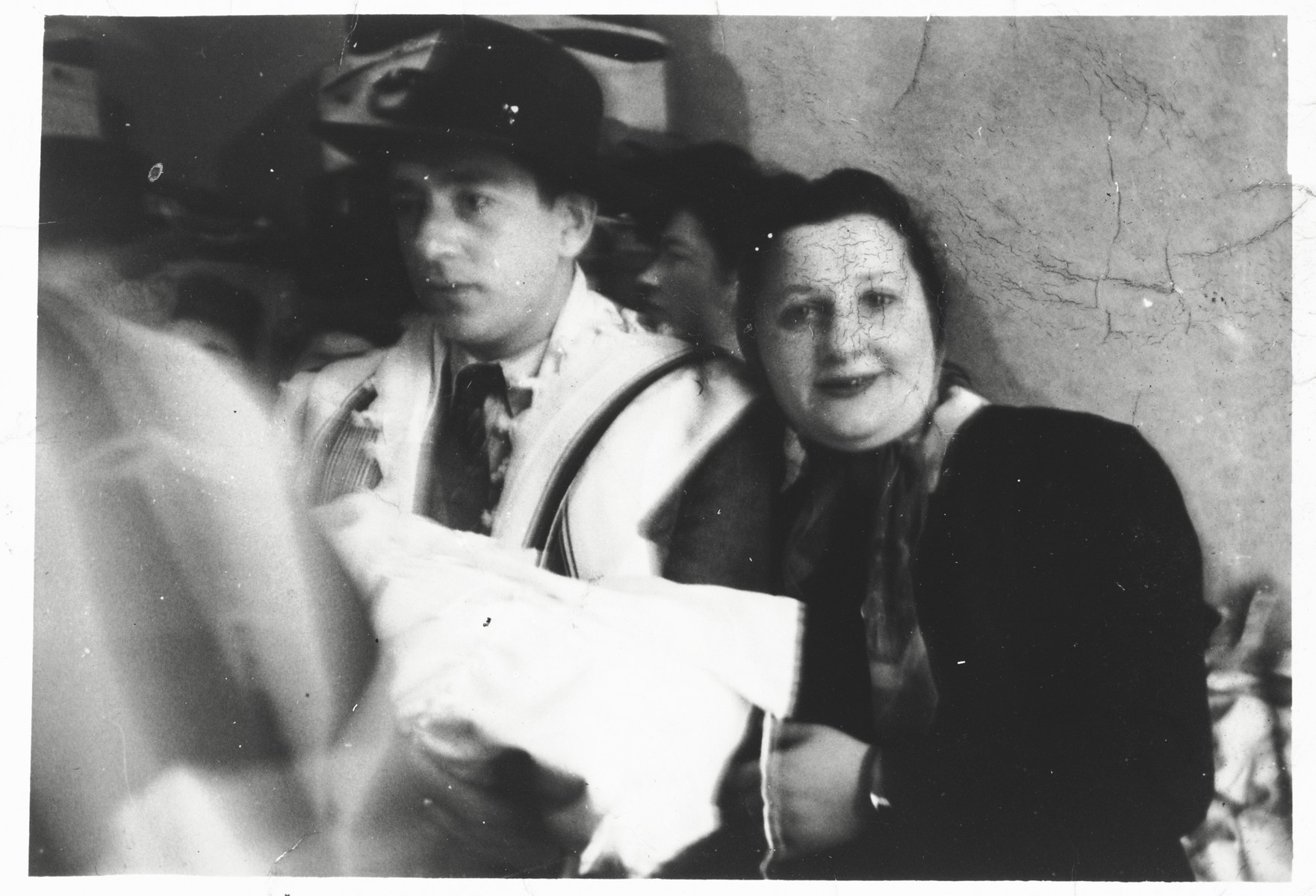 Itzhak Gendelman serves as the godfather at the circumcision of Arele Werkel, the son of Taibel and Yehiel Greenberg at the Ebelsberg displaced persons camp near Linz, Austria.  Among those pictured are Itzhak Gendelman (holding the baby) and Marim Broder.