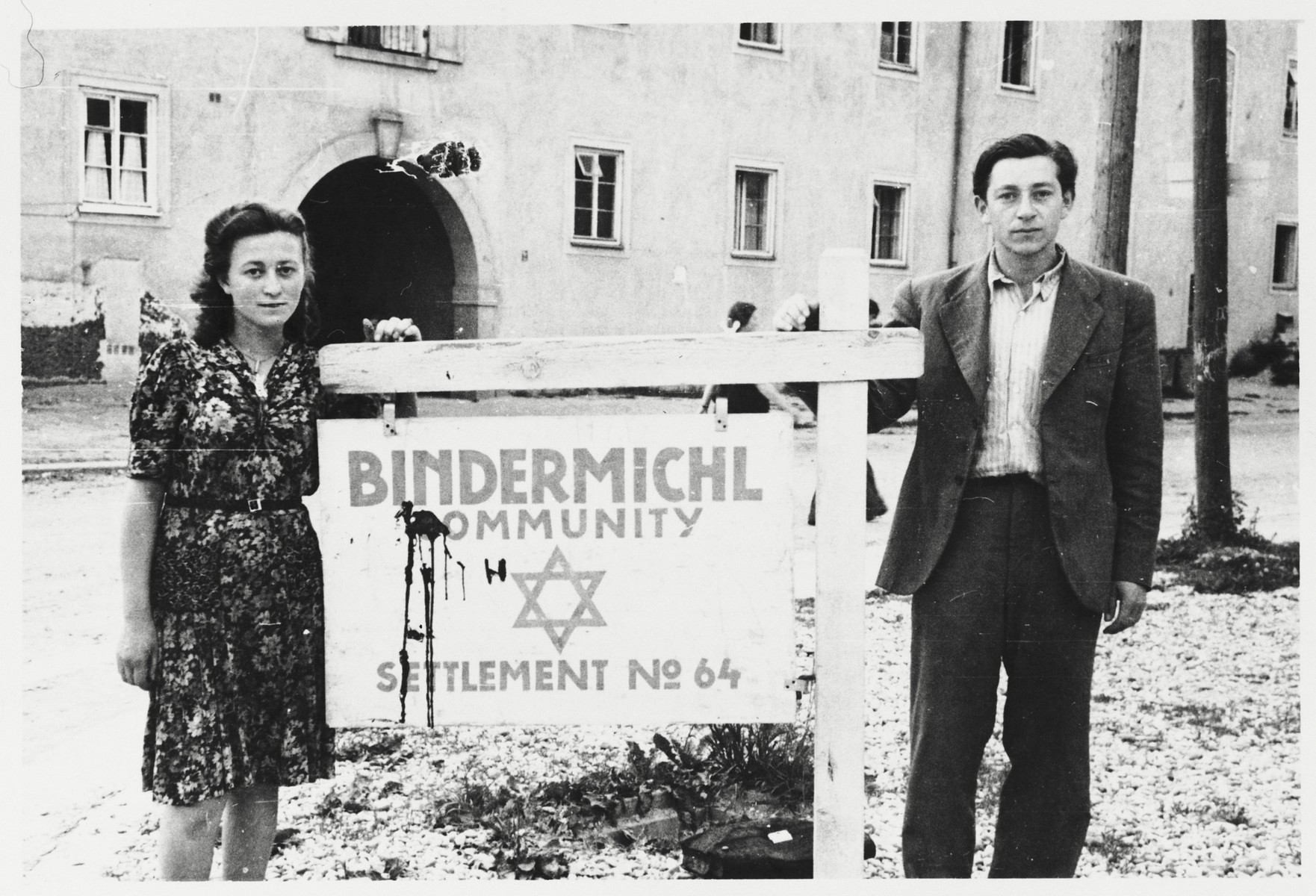 Two young Jewish DPs pose next to a sign at the entrance to the Bindermichl displaced persons camp near Linz, Austria.  Pictured on the right is Itzhak Gendelman.