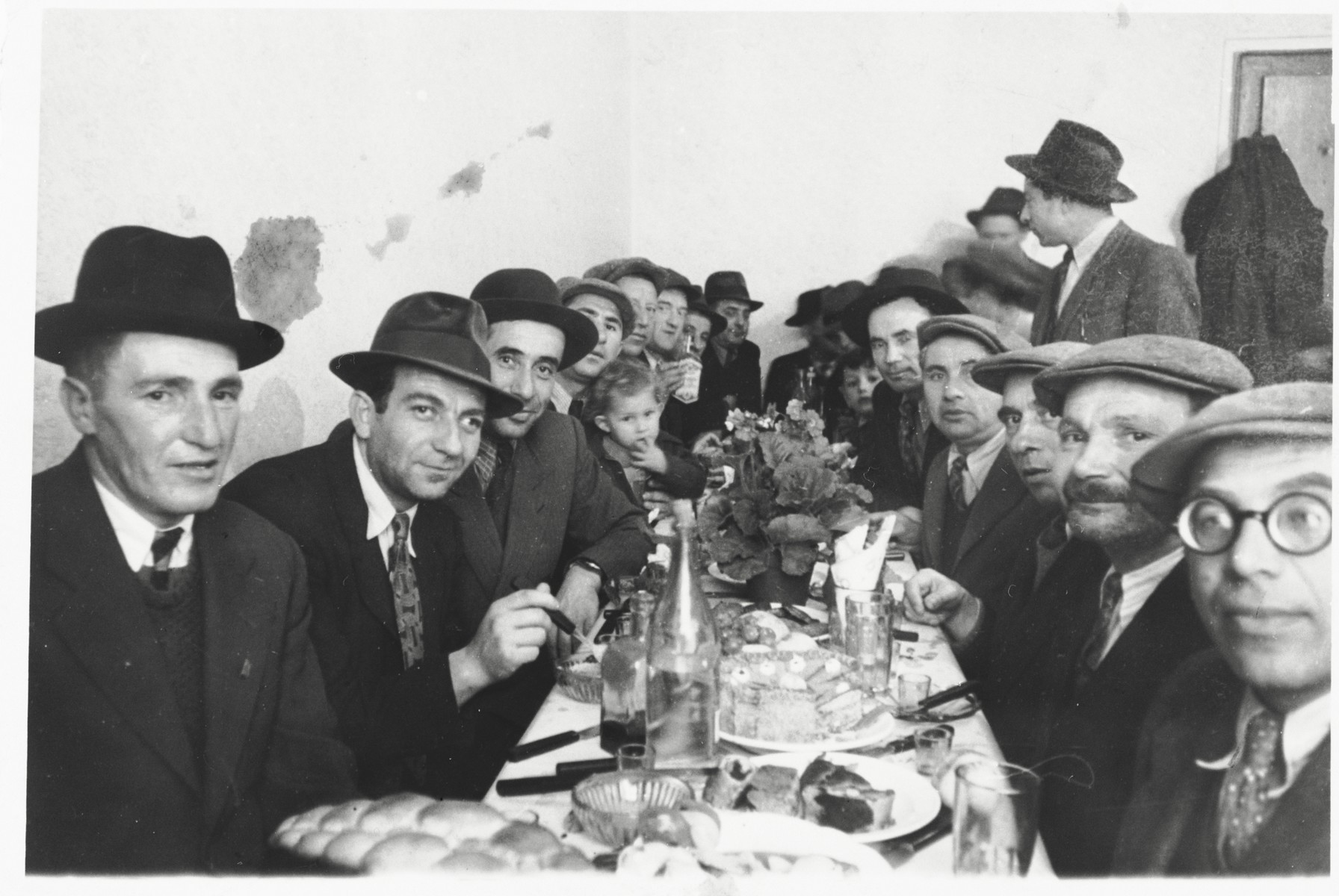 Jewish DPs are gathered around a table at a festive meal following the circumcision of Arele Werkel, the son of Taibel and Yehiel Greenberg at the Ebelsberg displaced persons camp near Linz, Austria.  Among those pictured are Itzhak Gendelman (standing at the upper right).