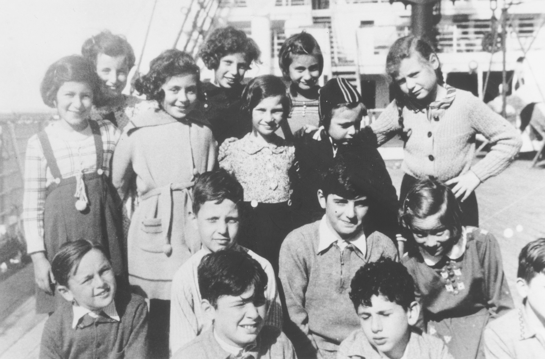 Group portrait of German Jewish refugee children on the deck of the SS Orama while en route to Australia.  Pictured are Marion Ehrlich, Ilse Frank, Margot Goldstein, Ellen Schaechter, Ellen Rothschild, Betty Abramson, Edna Lehmann, Jo Lehmann, Herman Gold, Rolf Taylor, George Dreyfus, Richard Dreyfus, Laurie Badrian, Ellen Lewinski and Alfred Stocks.