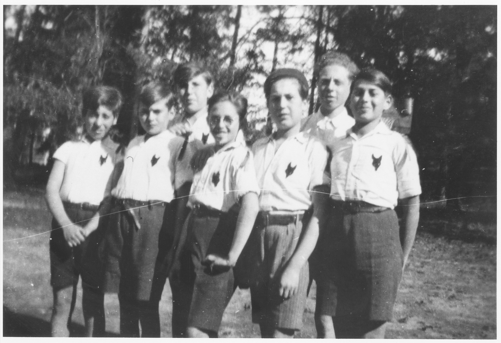 Group portrait of Jewish boy scouts in the Montintin children's home wearing shirts with wolf emblems.