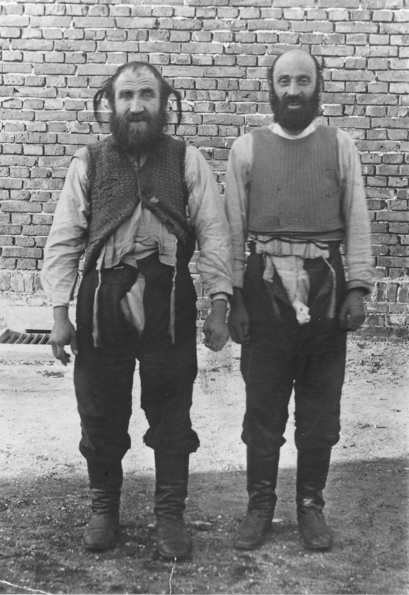 Two religious Jews are forced to stand outside in front of a wall with their pants open by German police prior to having their beards and sidelocks shorn.