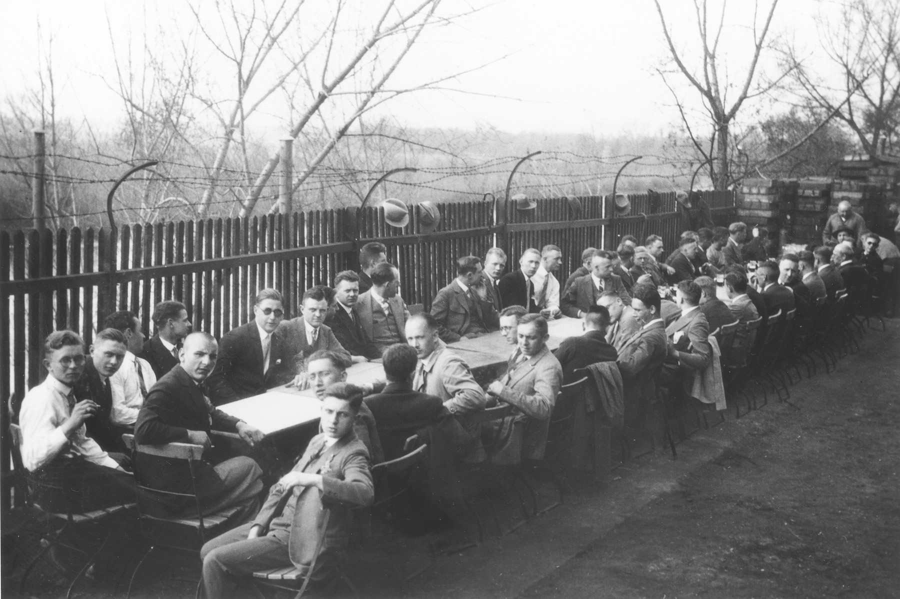 Herbert Mosheim (second from the left on the near side of the table) sits outside with members of his engineering class at the Städtische Erwerbshochschule.