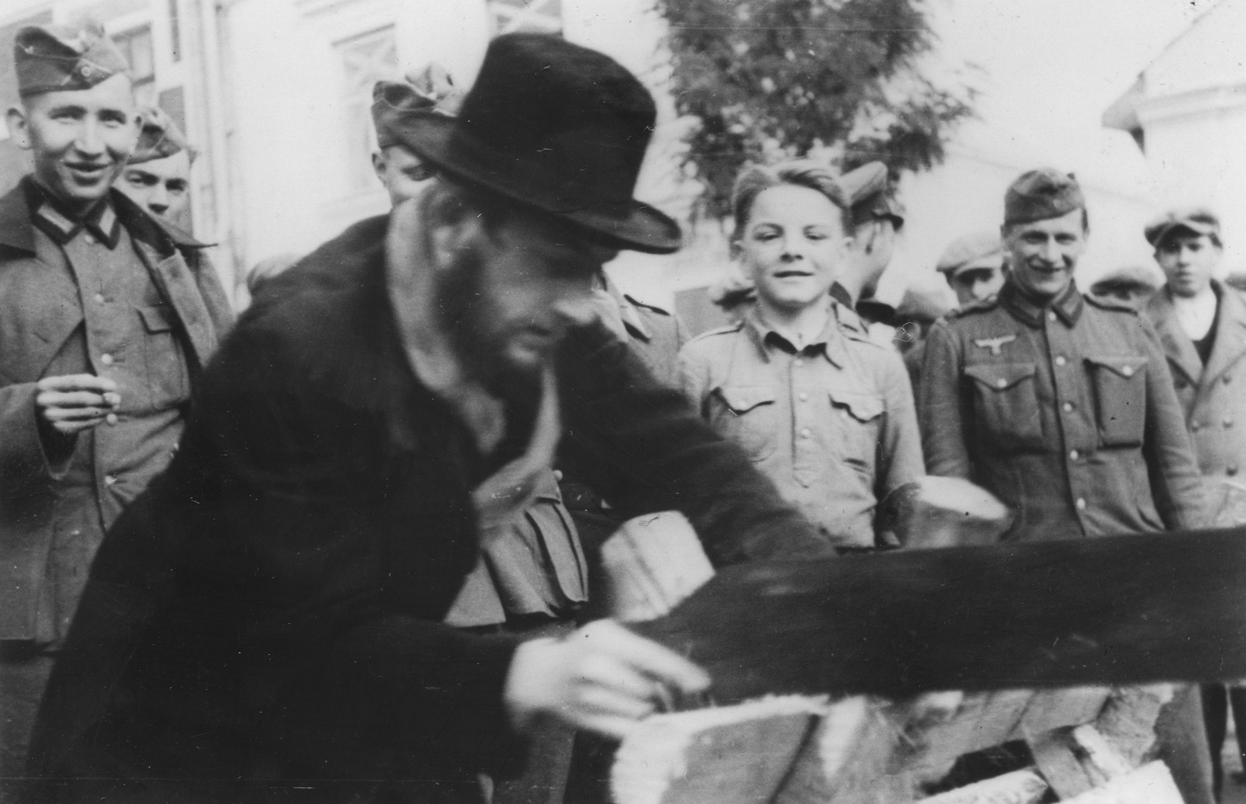 An observant Jew is forced to saw wood in front of a crowd of German spectators.