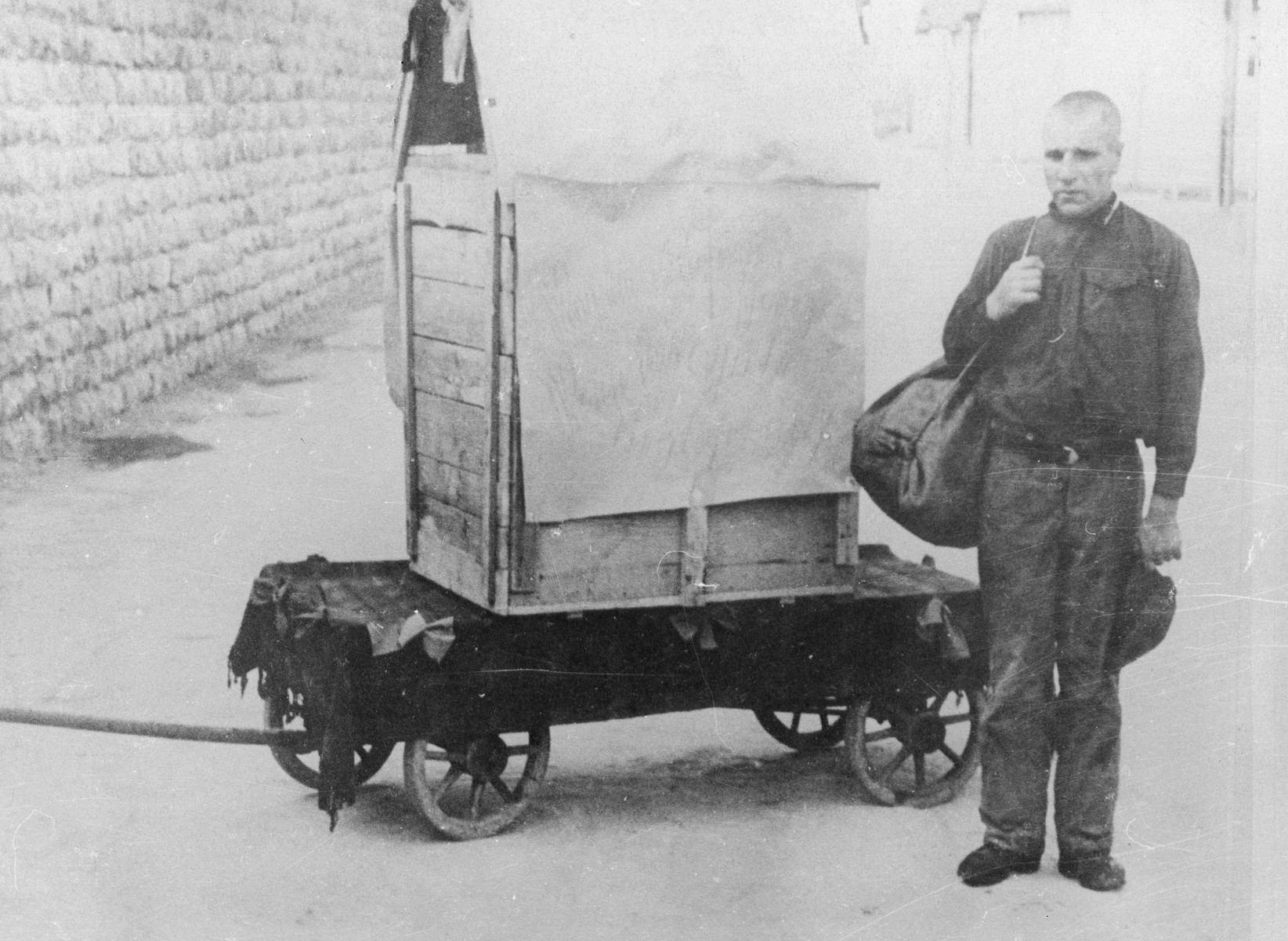 An escaped Mauthausen prisoner who has been apprehended by the SS is forced to pose next to the box in which he attempted his escape.  Pictured is prisoner Hans Bonarewitz.