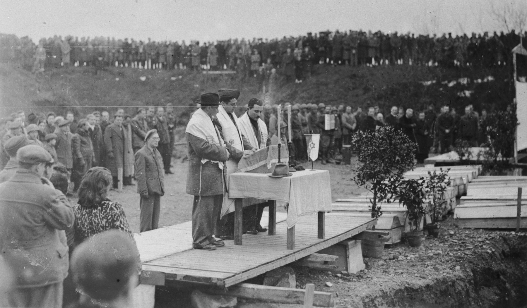 Three men draped in tallitot lead prayers at the dedication of a memorial at the site of the Pocking concentration camp.