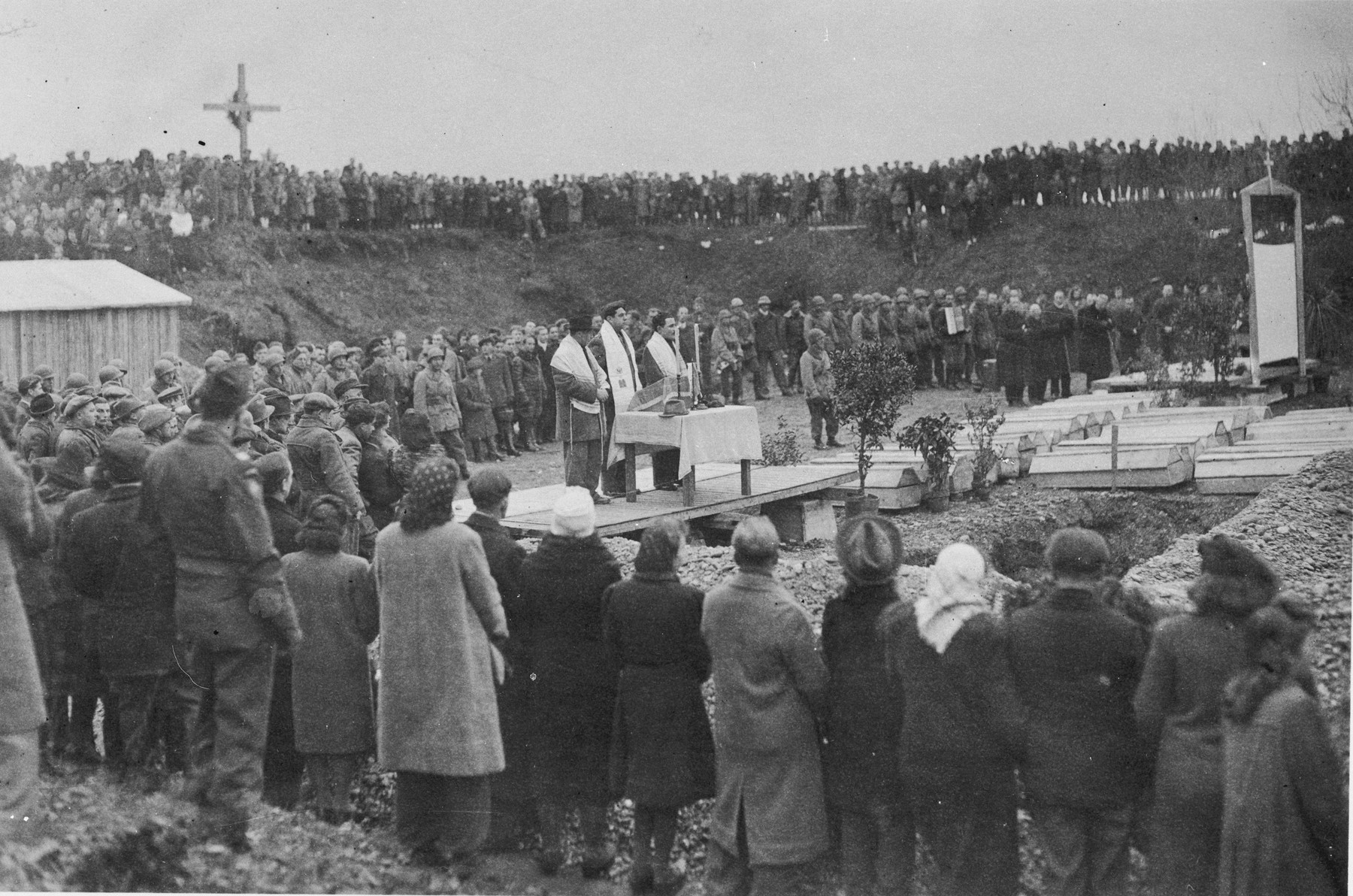 Three men draped in tallitot lead prayers at the dedication of a memorial and reburial at the site of the Pocking concentration camp.