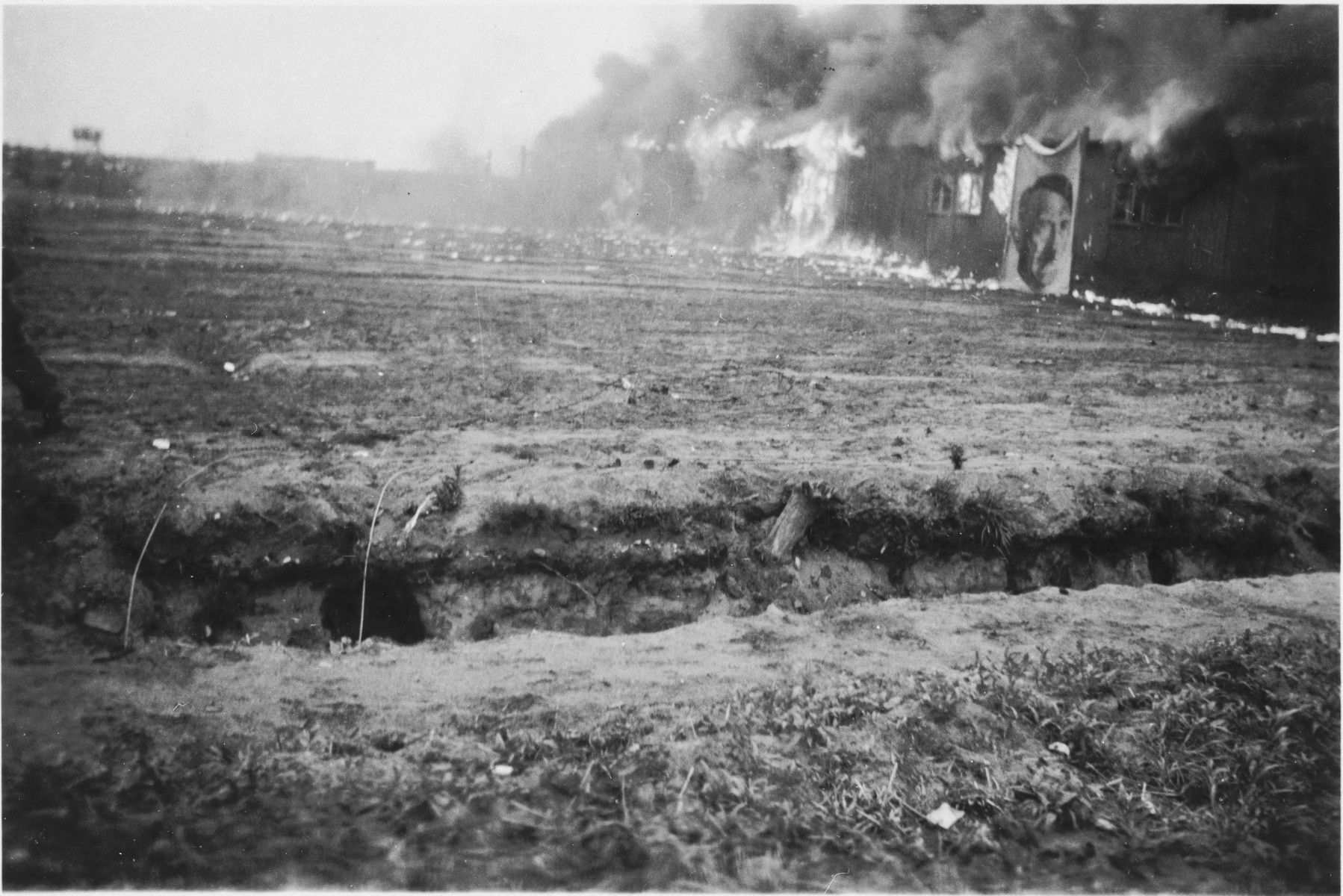 Fire consumes a barracks in the Bergen-Belsen concentration camp decorated with a wall size portrait of Adolf Hitler.    The barracks were burned to control the spread of epidemics.