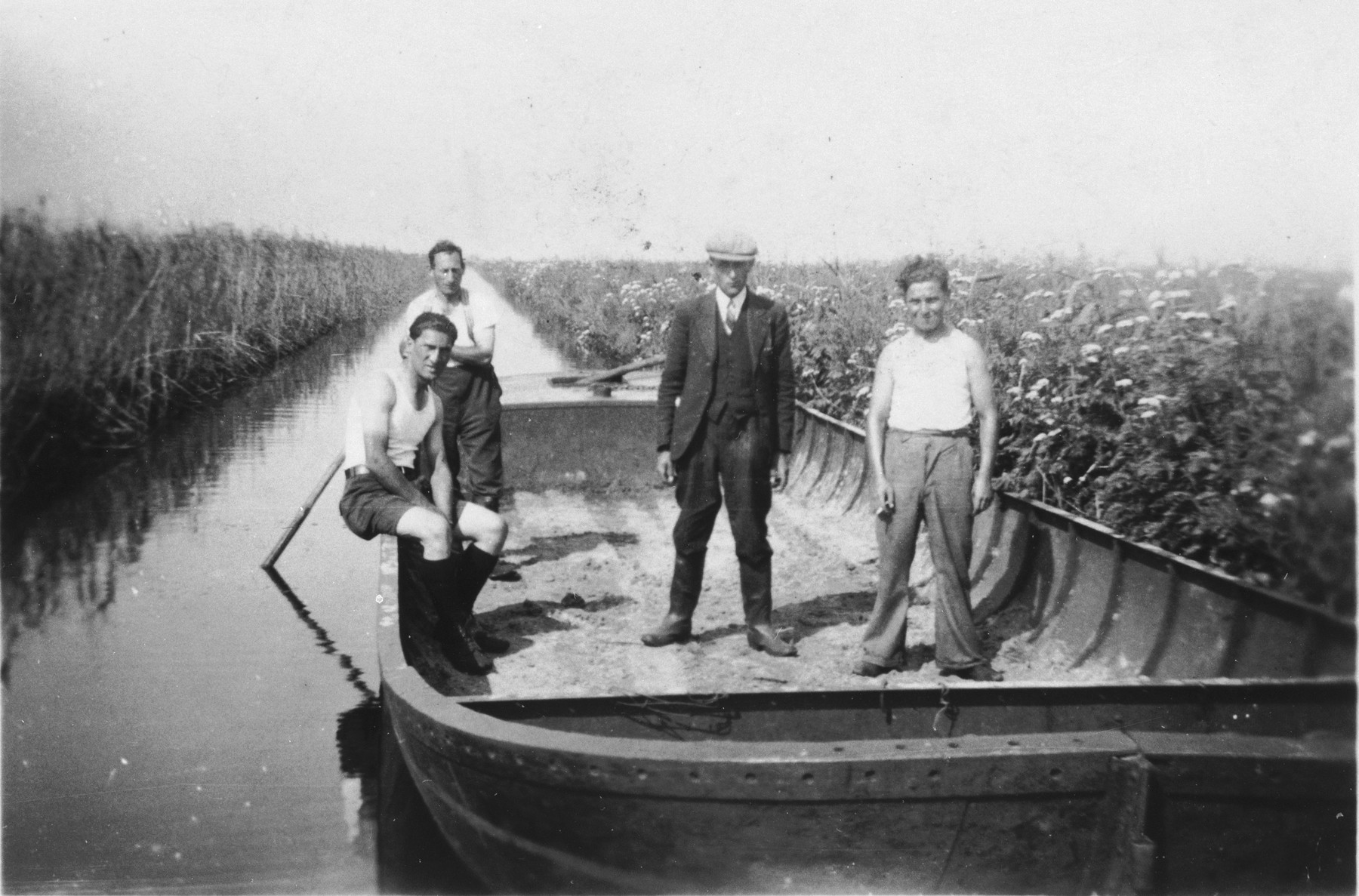 Prisoners pose on a barge that is in a canal that they are digging in the Staphorst-Rouveen labor camp.  Pictured from left to right are Coenraad Rood, M. Cohen, Boss Vruggink and Frenkel.