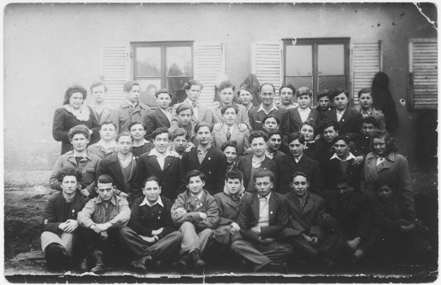 Group portrait of children from the Kloster Indersdorf children's home.  Among those pictured are Erwin Farkas, Fred Stern, Walter Hahn, Berek Feldbaum, Adolph Weiss, Druecker and Michael Roth.  Genia Edlerman (Jean Sugar) is seated in the center, front row. To her right is her brother, Nechemia Edlerman. Roman Kniker is directly in center (fourth person from both the left and right sides) in the front row. Niderman is the first person on the left in the second row. Herbert Hahn is seated next to him. Erwin Farkas is third from the right in the second row. Avraham Leder is the first person on the right in the third row. Naftali Steinberg is seated next to him. Walter Hahn is the first person from the left in the third row (center of picture where row begins). Michael Roth is the fourth person from the right in the last row. Jakub Kerker is the third person from the left in the last row. Ivan Kisz is the fourth person from the left in the last row.  Alfons Weber is also pictured.