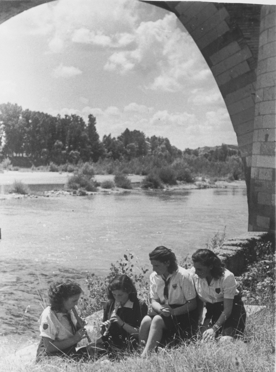 A group of girl scouts play recorders on a riverbank.   Edith Loeb, a Jewish girl in hiding, is pictured on the far right.