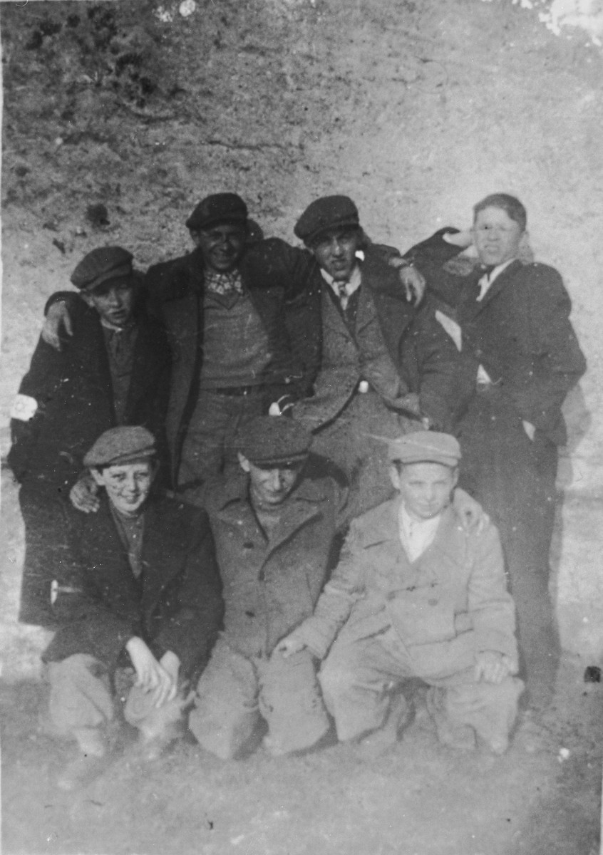 A group of boys wearing armbands pose together in the Nowy Targ ghetto.  Pictured are Benek Kalfus, Romek Reibeisen, Emil Kalfus, Romek Stater, Moniek Weiss, Poldek Lewenberg and Heniek Feler.