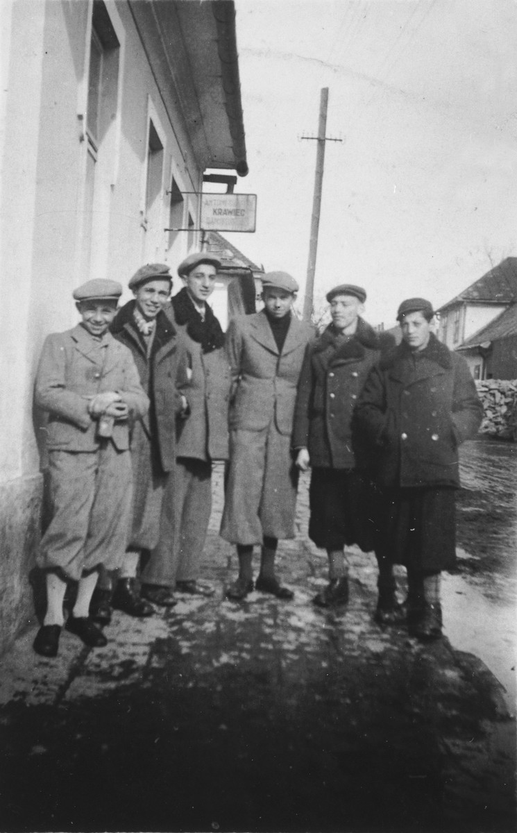 A group of boys stands on a street corner n Nowy Targ.