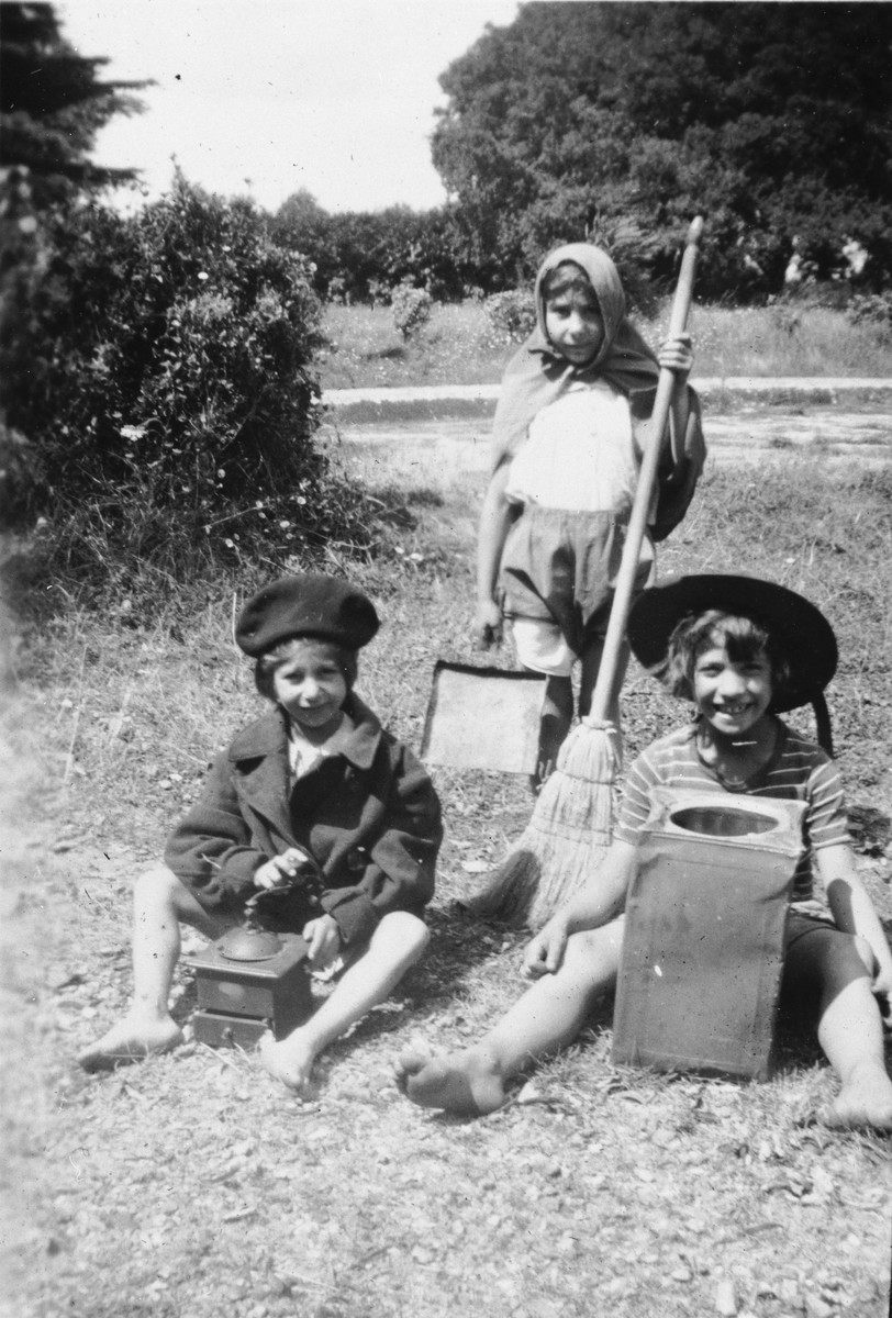 Three young children dressed in old fashioned hats pose with various household tools in the garden of the Mehoncourt children's home.