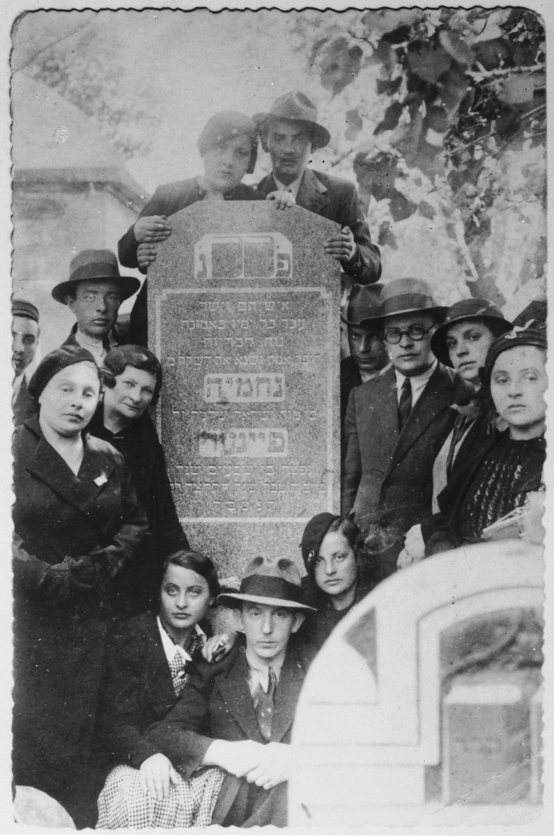 Unveiling of the tombstone of Nehemia Feiner, the donor's maternal grandfather.   Pictured clockwise from the bottom left are: Rozalia Luksenburg; Freidl Feiner; Moryc Feiner; Ada Koziwoda; Feliks Koziwoda; Izydor Feiner; his wife; Mrs. Chmielnicka; Raila Spiro; Josef Kerner and Stefa Kerner.  Also shown partially cut off on the left is Yehiel Feiner (aka Katzetnik).