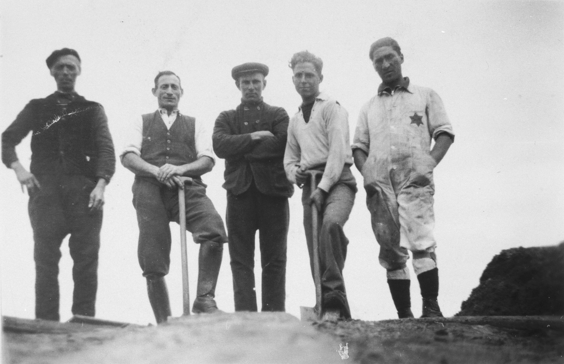 Group portrait of two Dutch Jews and three paid Dutch workers in the Staphorst-Rouveen labor camp.  Coenraad Rood, the donor, is standing first from right and Moses Cohen is second from left.