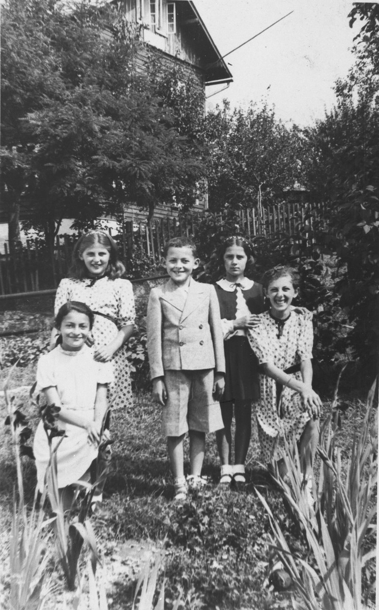 Serafina Strasser poses in a garden with her sister Pola and a group of friends.