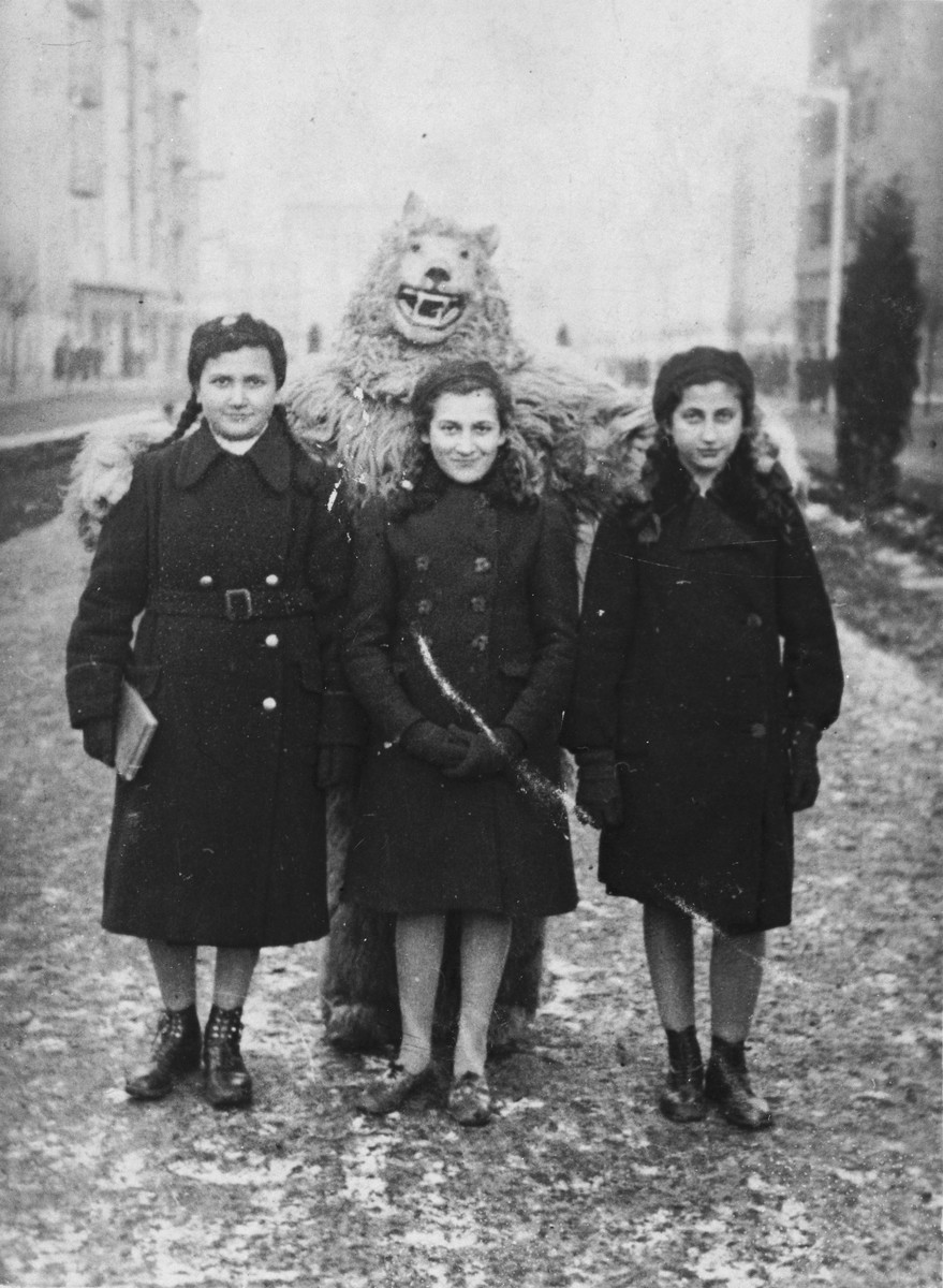 Hinda Chilewicz (middle) and her two cousins, Edzia (left) and Hadasa Cudzynowski (right) pose with a bear.