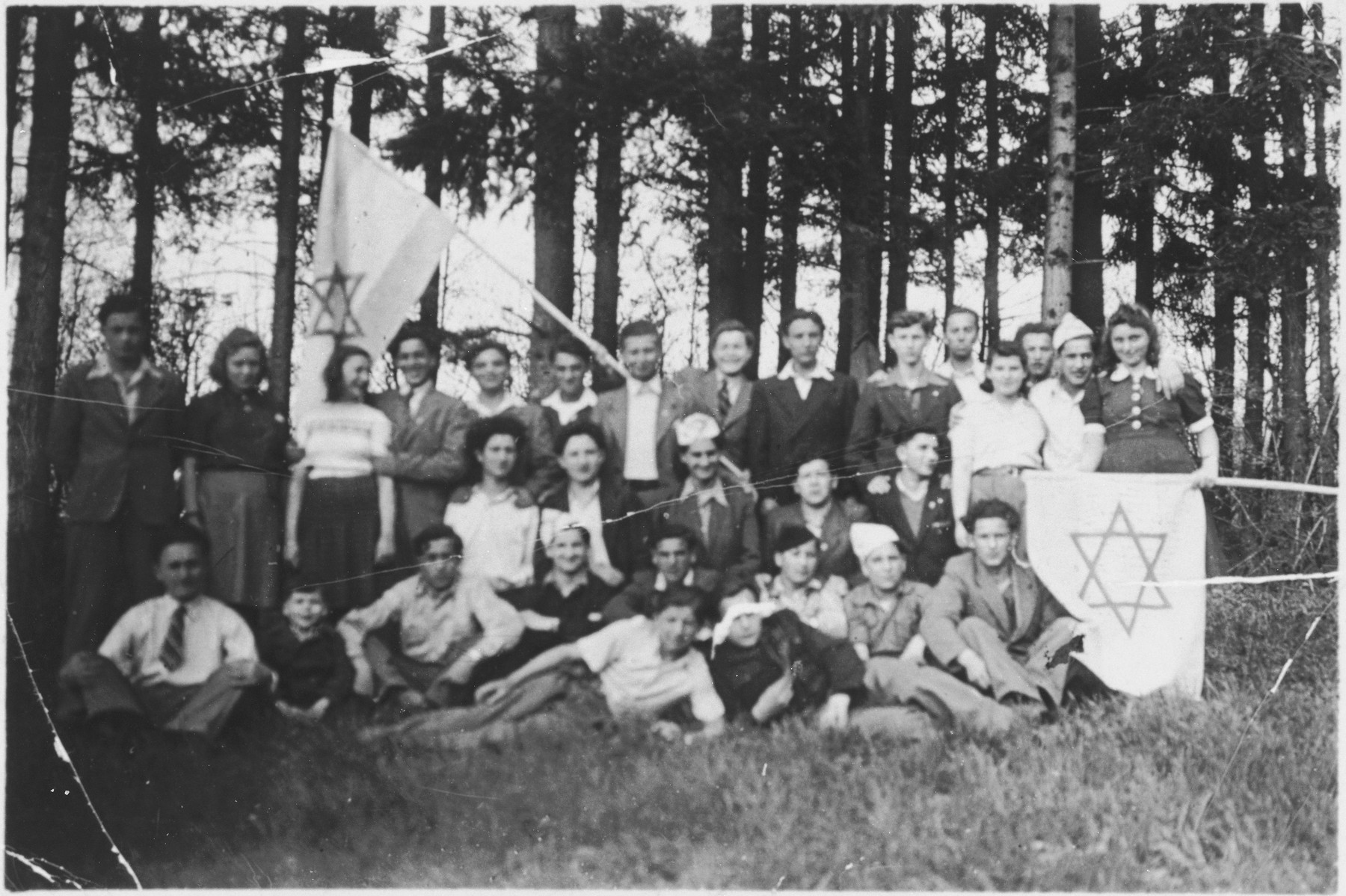Jewish children from Kloster Indersdorf go on an excursion in the woods while carrying Zionist flags.