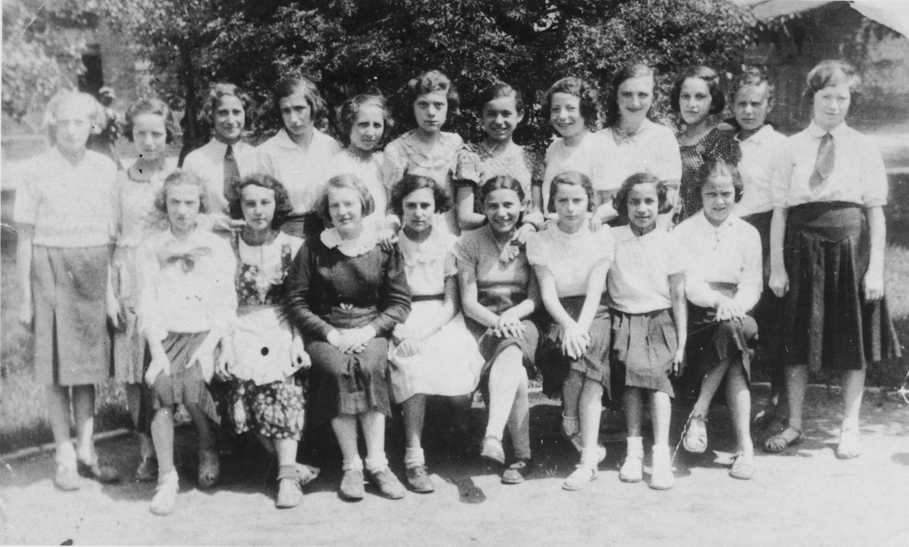 Class portrait of 7th grade students at a Jewish public school in Sosnowiec.    Pictured in the front row (left to right) is unknown; Lusia Szpiro; unknown; ? Borensztajn; unknown; Jadzia Szyjewicz; Mania Zaks; and Edzia Bank. Standing in the back row is Rutka Rabino (sixth from the left) and Helen Glejtman (fourth from the right).