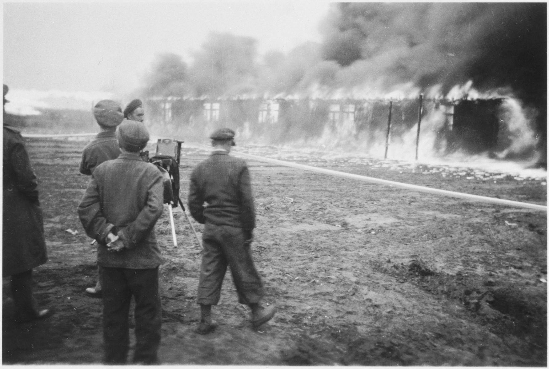British soldiers watch as fire consumes a barracks in the Bergen-Belsen concentration camp.  The barracks were burned to control the spread of epidemics.