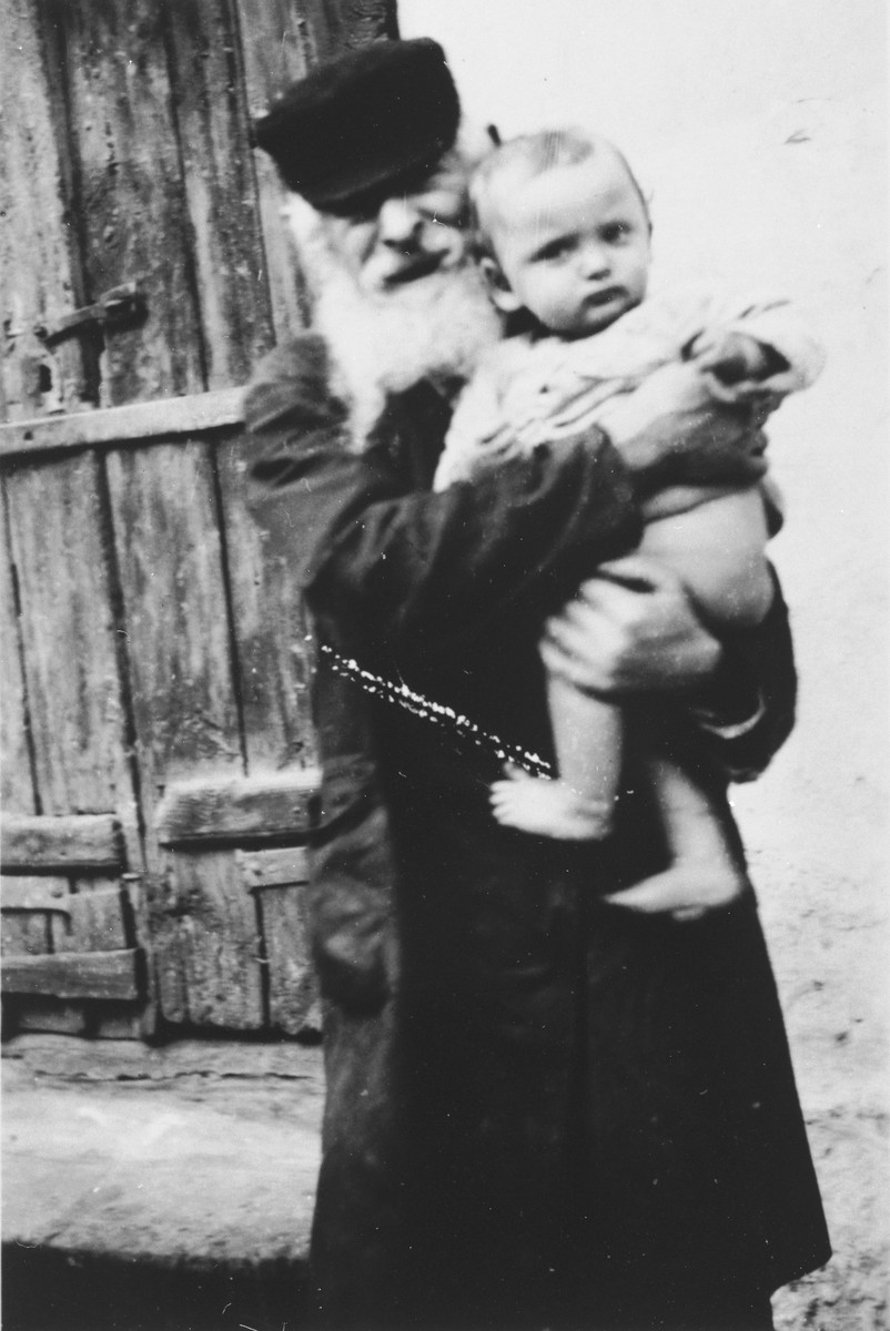 "An elderly Jew holds a small baby in an unidentified ghetto in Poland.  The photograph, which had been in the possession of a member of the SS bears the caption, ""like the old one, so the young""."