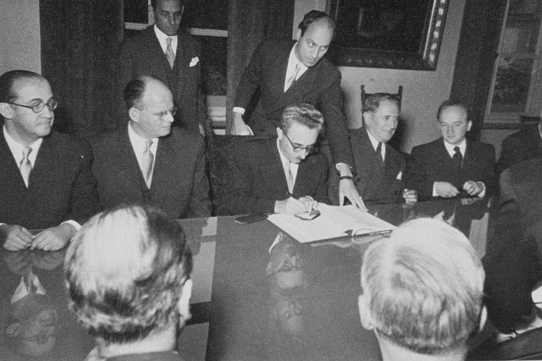 Israeli Foreign Minister Moshe Sharett signs the Reparations Agreement between the German Federal Republic, the State of Israel, and the Conference on Jewish Material Claims.    Seated from left to right are: Felix Shinnar, Giora Josephthal, Moshe Sharett, Nahum Goldmann, and Benjamin Ferencz.