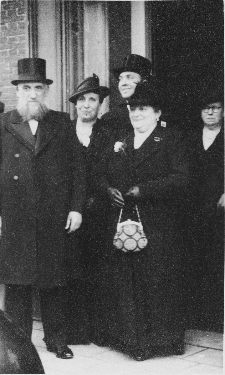 Rabbi Eliyahu Frances, chief rabbi of the Portuguese Synagogue in Amsterdam, and his wife Diamante Tazartes stand in front of a group of people leaving the synagogue.  Standing in the back is his son, Jacques Frances.  He survived, but his parents Rabbi Eliyahu Frances and Diamante Tazartes and their youngest son Daniel were killed in Monowitz in 1942.