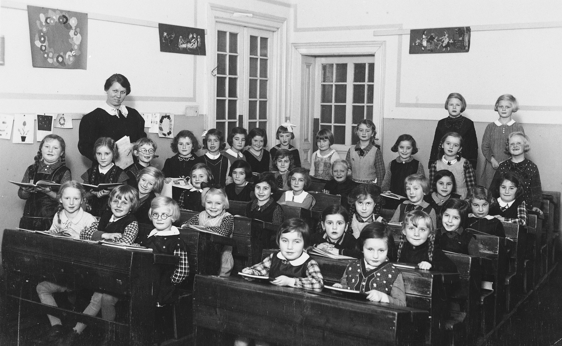 Austrian and Jewish children in the Schubert Schule in Vienna.  Pictured on the far left is the teacher, Hansi Lang.  Eva Weitzmann is seated in the fourth row, second from the right.
