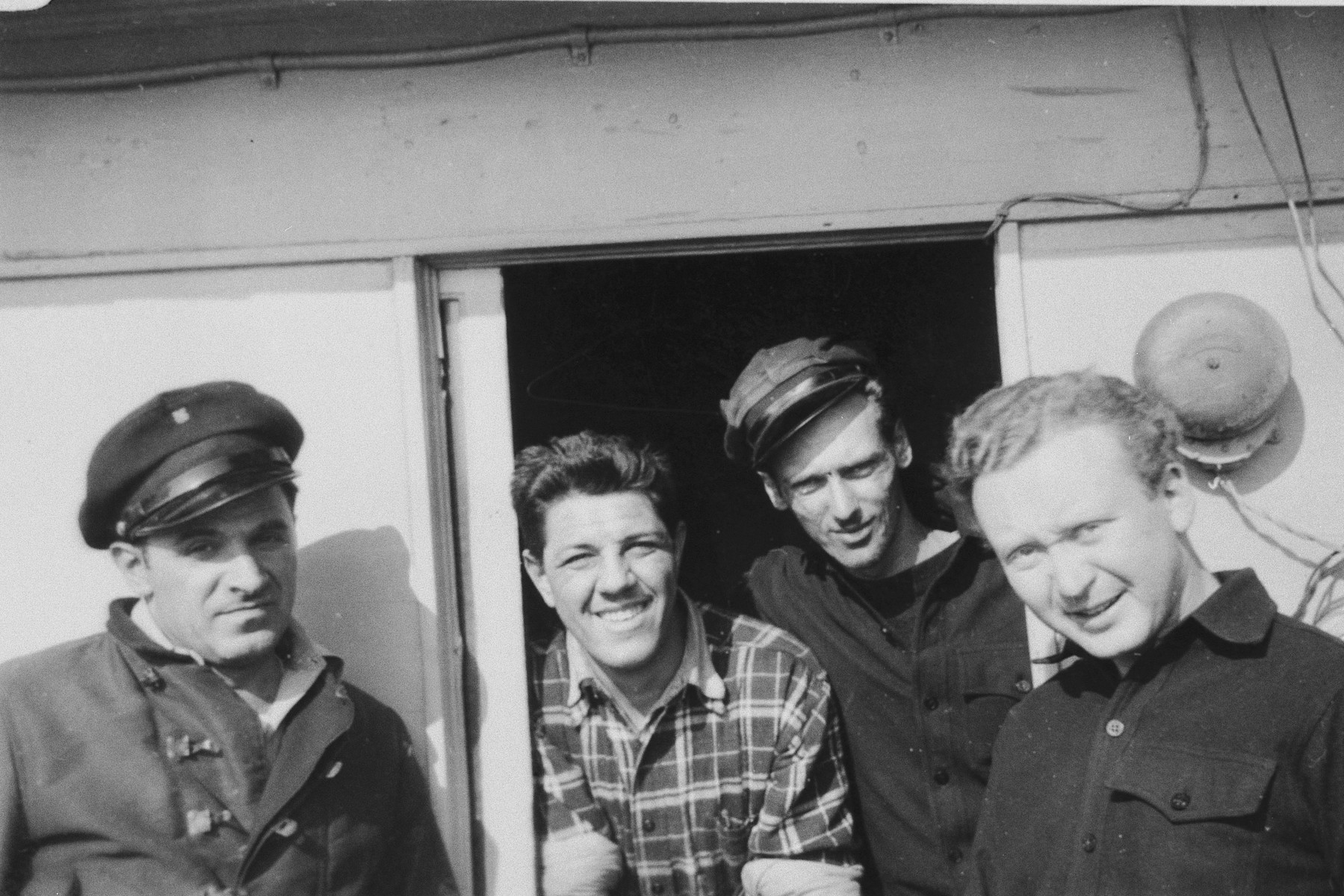 Four crew members of the President Warfield (later the Exodus 1947) pose on the deck of the ship in Baltimore harbor.  Pictured from left to right are: Mike Weiss, William Millman, Paul Yarin and William Bernstein.
