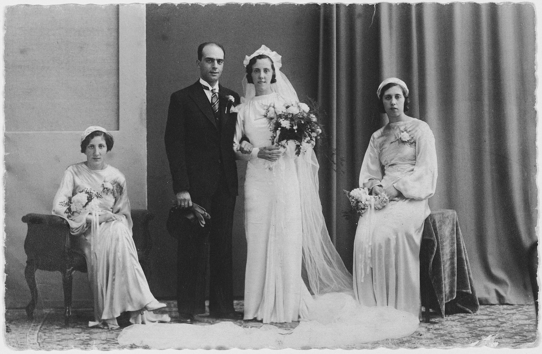 Wedding portrait of Daniel and Clara Frances flanked by two bridesmaids.