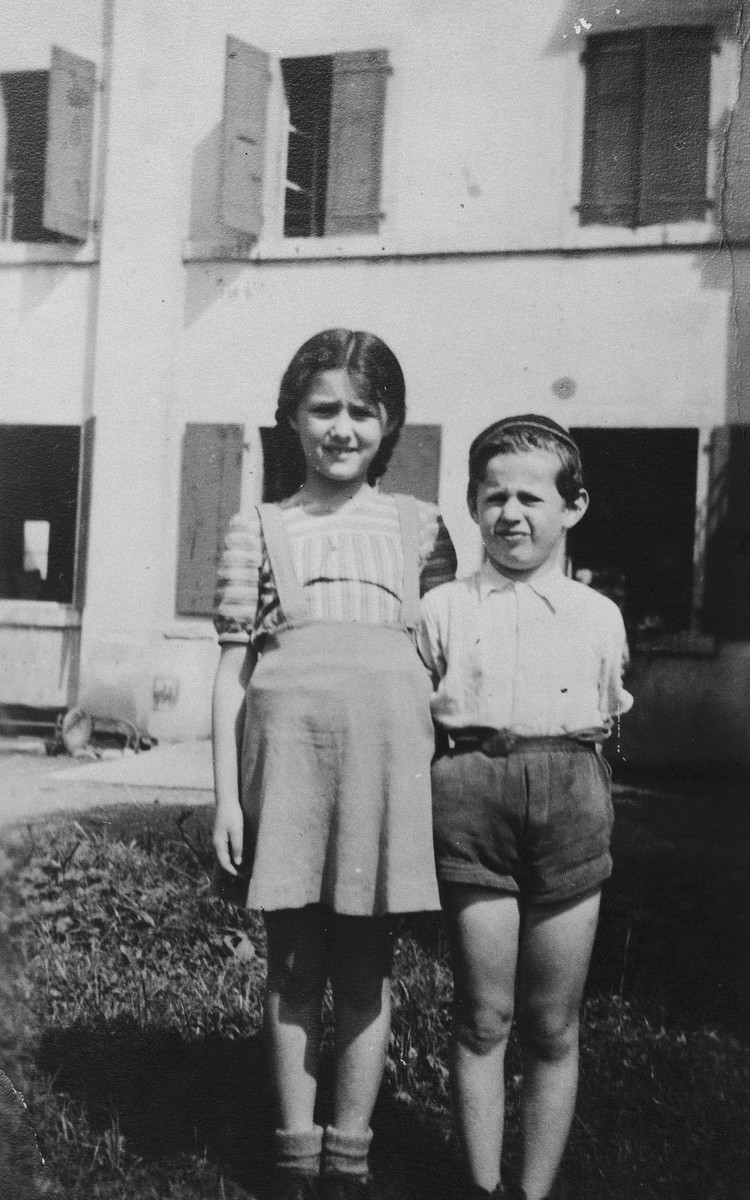 Two Jewish refugee children from Antwerp, Belgium, pose outside their children's home in Bex-les-Bains where they stayed after fleeing to Switzerland.  Pictured are Markus and Annie Wajsfeld.