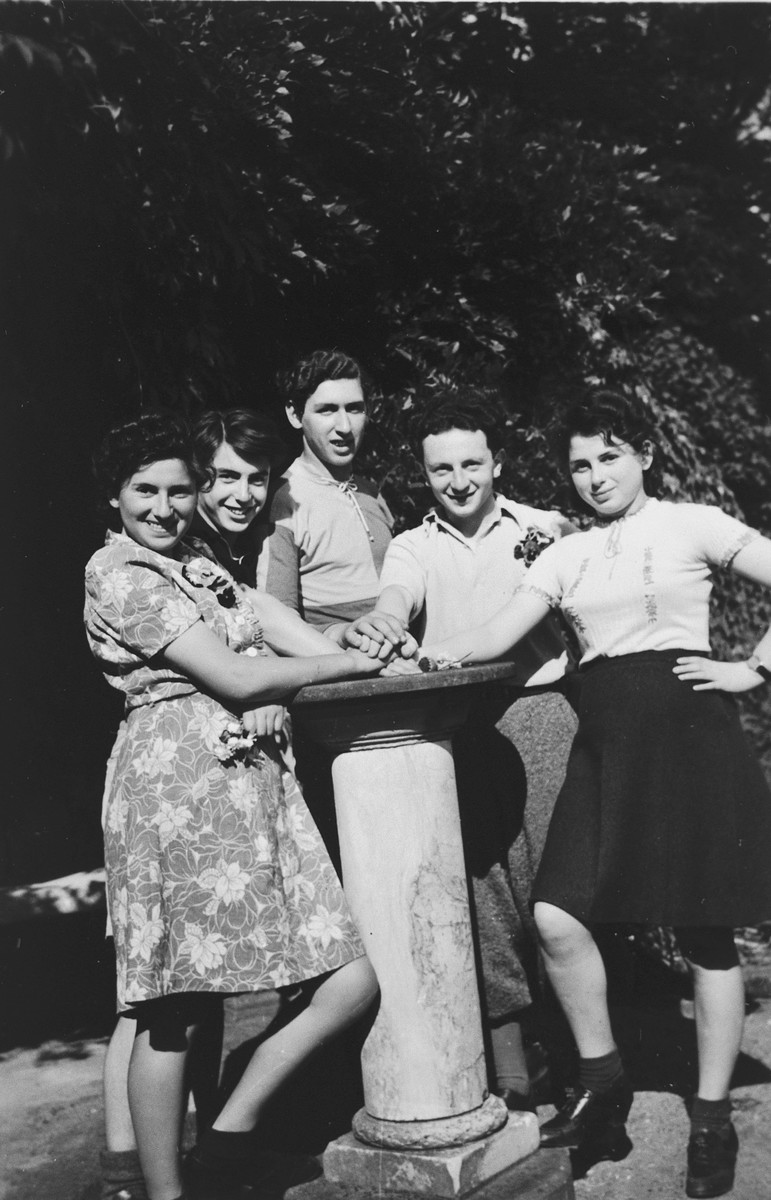 Five teenagers from the Blankenese children's home pose next to a stone pillar.  Among those pictured is Moniek Izbicki.