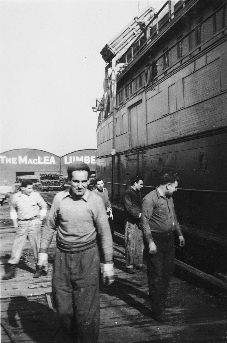 A crew member of the President Warfield (later the Exodus 1947) walks along the pier next to the ship  Pictured is Eli Kalm, chief steward of the ship.  (Eli Kalm was self-taught and fluent in both French and Italian from having studied opera libretto.)