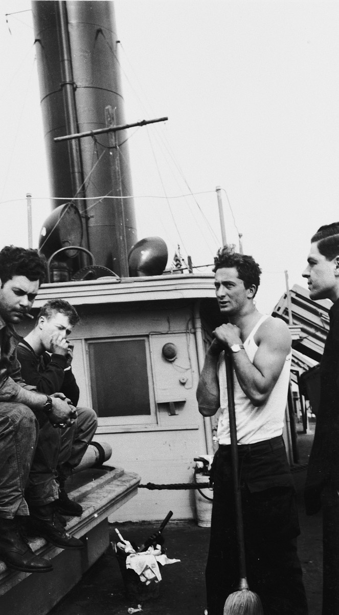 Four crew members on the deck of the President Warfield (later the Exodus 1947) in Baltimore harbor.  Pictured are Harry Weinsaft, Bentley Forman, Murray Aronoff and Avi Livney.