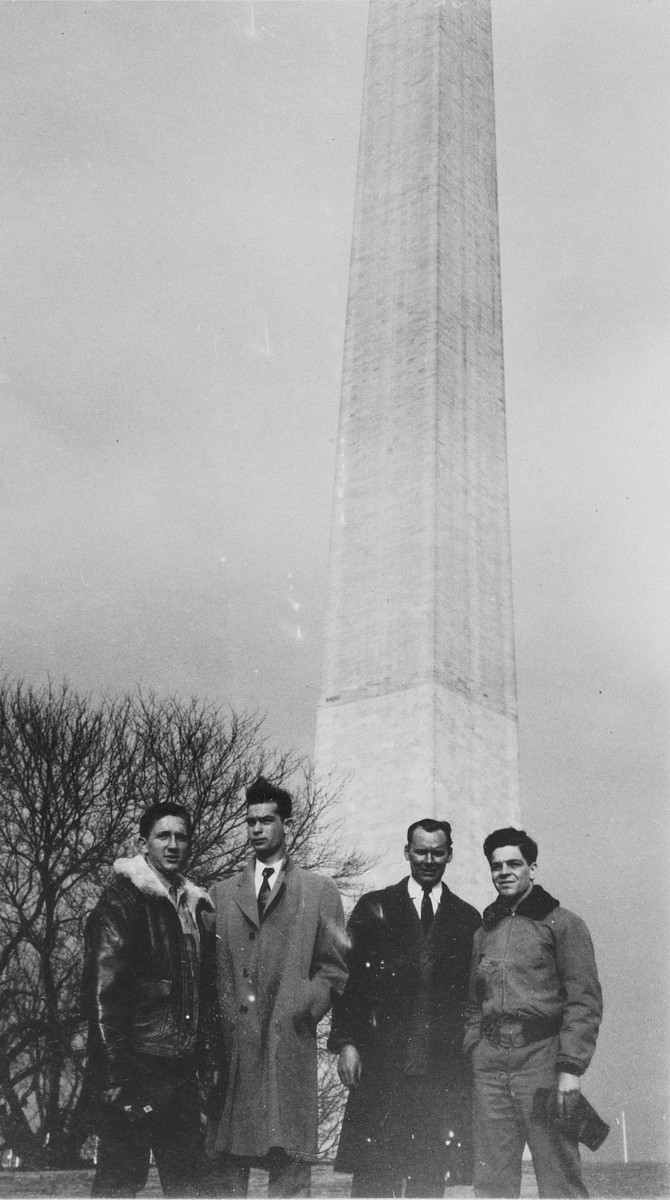 Four crew members of the President Warfield (later the Exodus 1947) pose in front of Washington Monument in Washington, DC.  Pictured from left to right are: Reuben Margolis, Yaakov Oron, John Grauel and Avi Livney.
