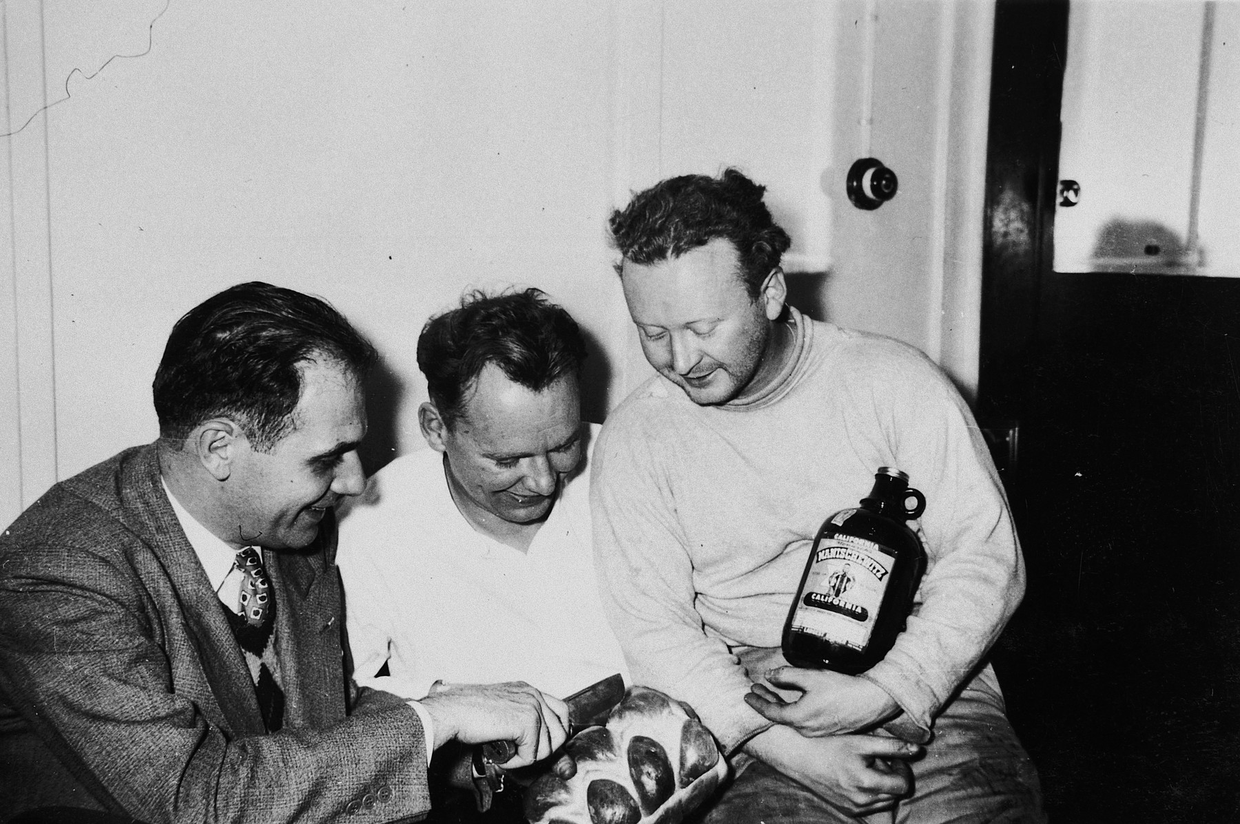Crew members of the President Warfield (later the Exodus 1947) prepare for a Sabbath dinner in Norfolk, VA.  Pictured from left to right are: Nat Cohen, John Grauel and William Bernstein.