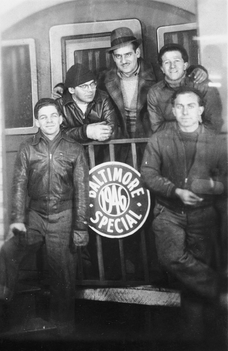 "Five crew members of the President Warfield (later the Exodus 1947), pose around a sign that reads ""Baltimore 1946 Special"" in Baltimore.  Pictured from left to right are: Avi Livney, Shmuel Beeri (Baer), Eli Kalm, Itzhak Aronowitz and Cyril Weinstein."
