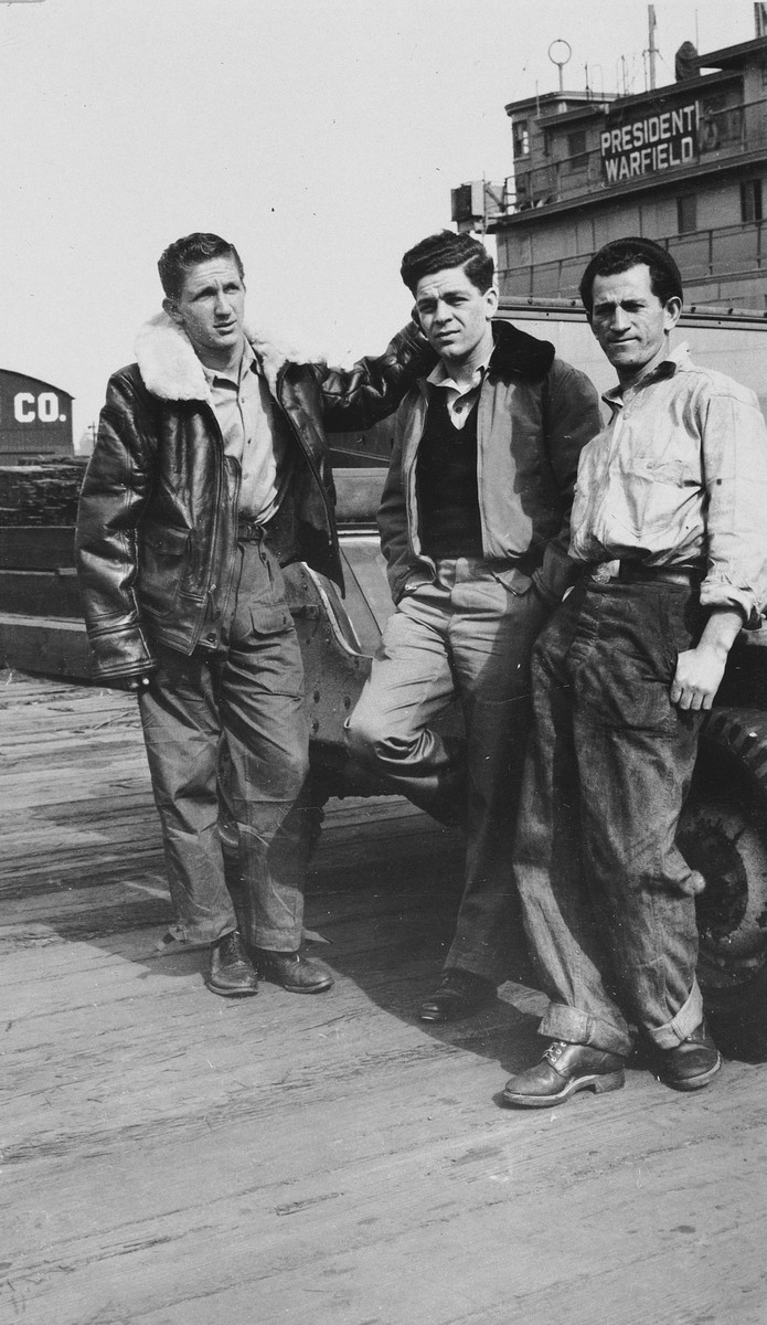 Three crew members pose on the pier in front of the President Warfield (later the Exodus 1947) in Baltimore harbor.  Pictured in the center is Avi Livney.  He is flanked by two Mexican crew members, Reuben Margolis (left) and Avraham Siegel (right).