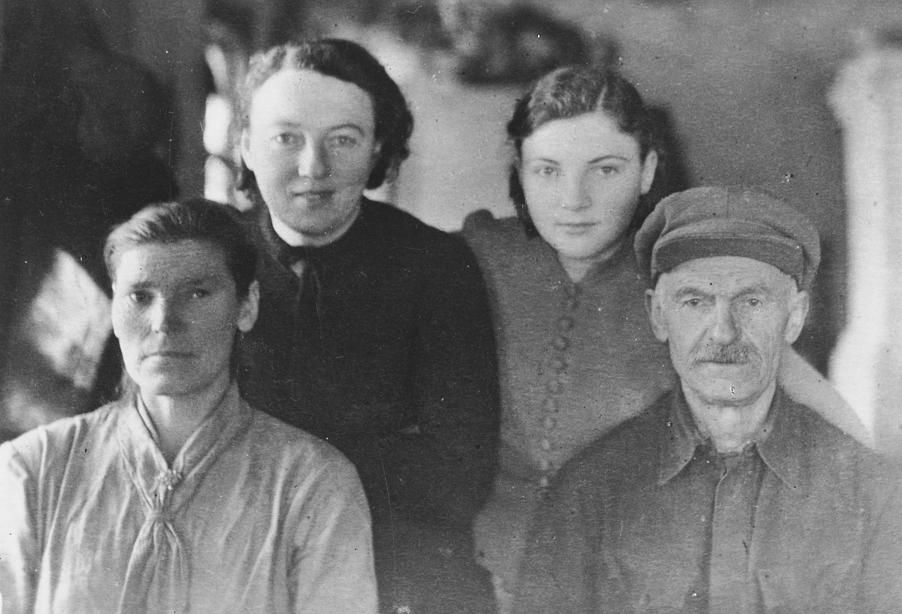 Genia and Helena Storch pose with the Russian couple with whom they lived while in exile in Zhuravlovka.