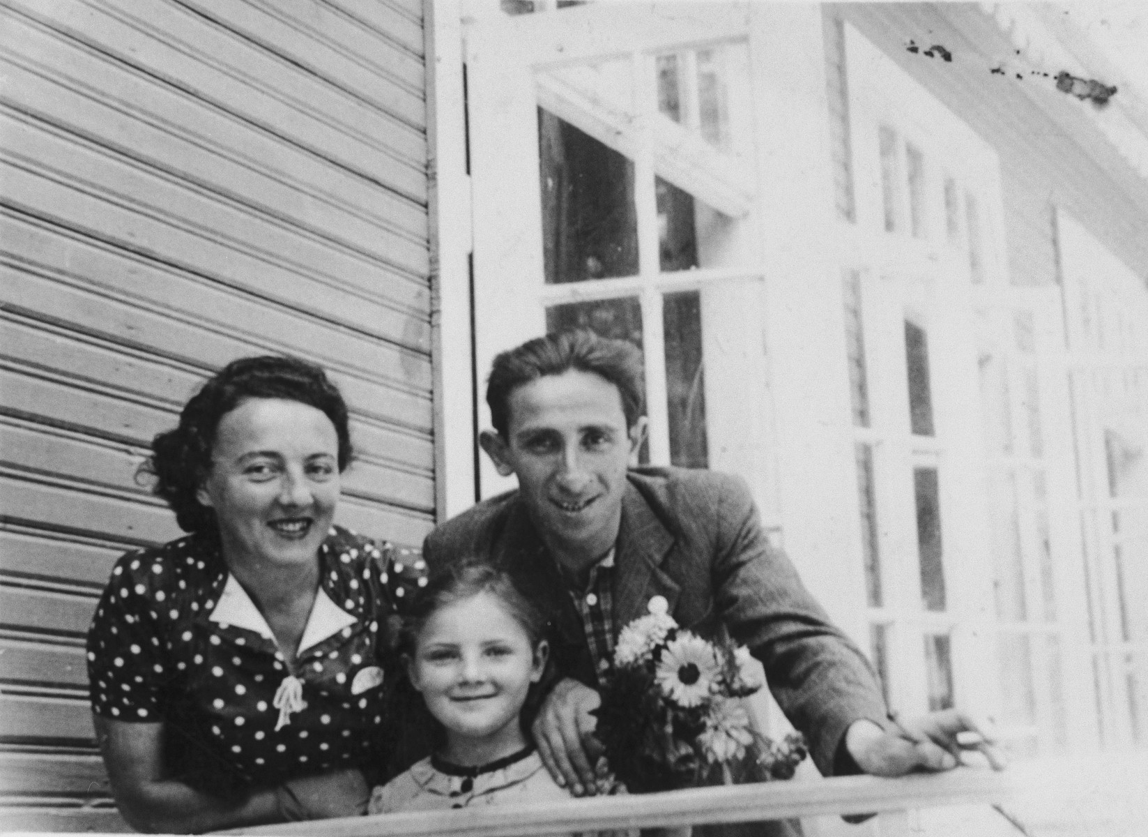 The Storch family looks over the railing of a guest house in Domaczewo.  Pictured are Heniek, Genia and Helena Storch.  This is the last holiday Genia and Helena spent with Heniek.