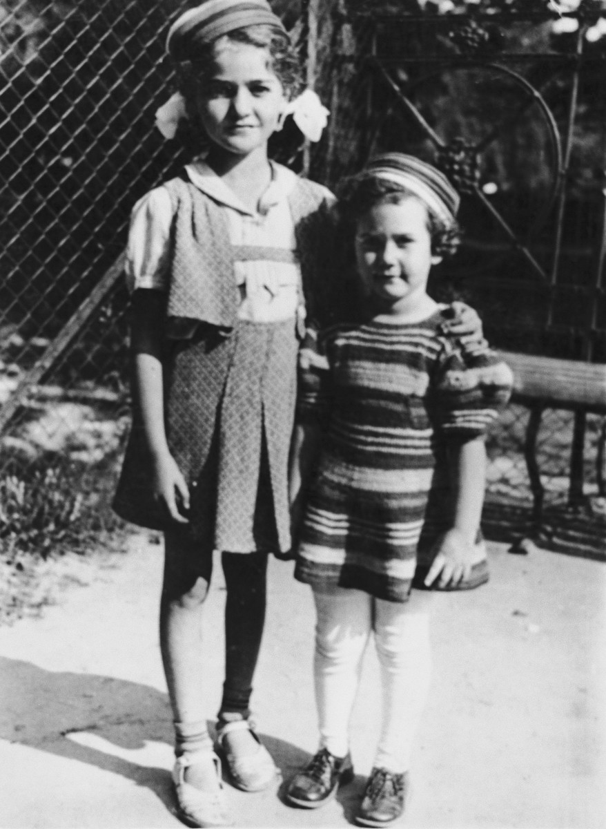 Two young cousins pose with their arms around each other.  Roma Glowinski is on the left.  Her cousin Neta is to her right.