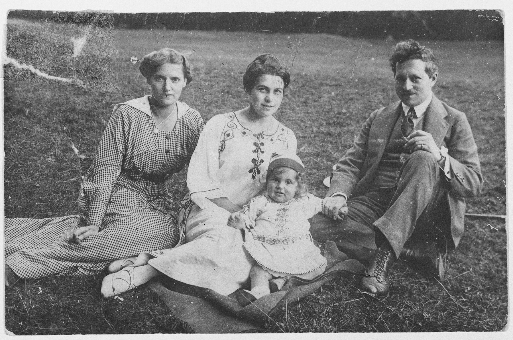 The Singer family poses for a portrait on a grassy field.  Pictured are a nanny, Gertrude, Margot and Kurt Singer.