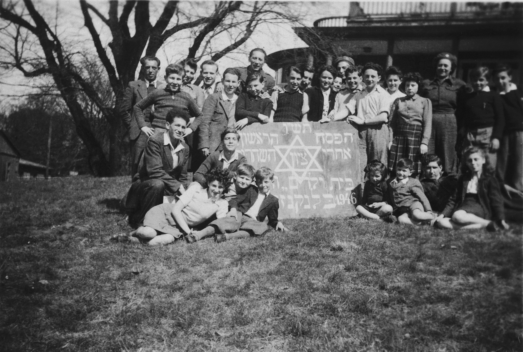 "Children from the Blankenese children's home pose next to a large sign reading ""the first Passover after liberation.""  Among those pictured is Moniek Izbicki."