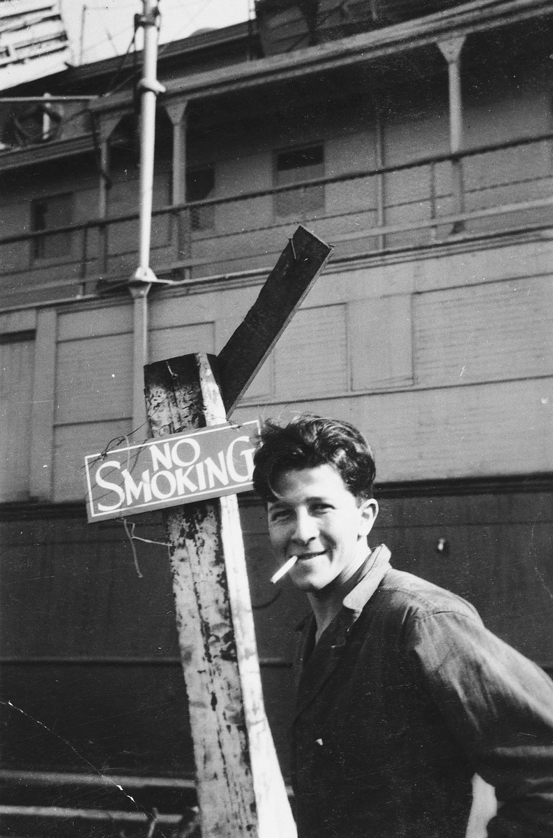 "Itzhak Aronowitz, chief mate and later captain of the President Warfield (later the Exodus 1947), lights up a cigarette in front of a ""no smoking"" sign in Baltimore harbor."