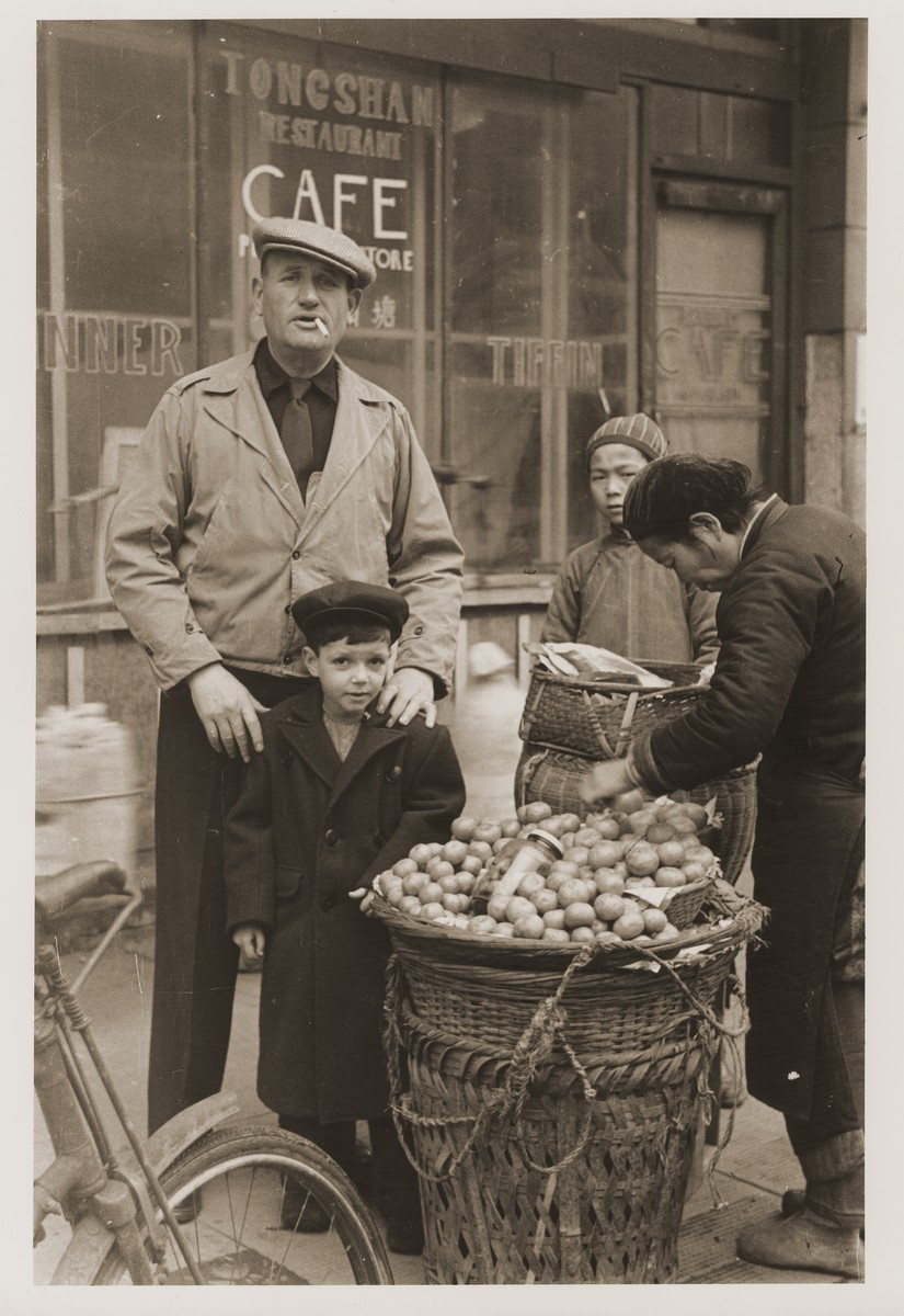 Jewish refugees Harry Fiedler and Heim Leiter pose next to a potato vendor on a Shanghai street.