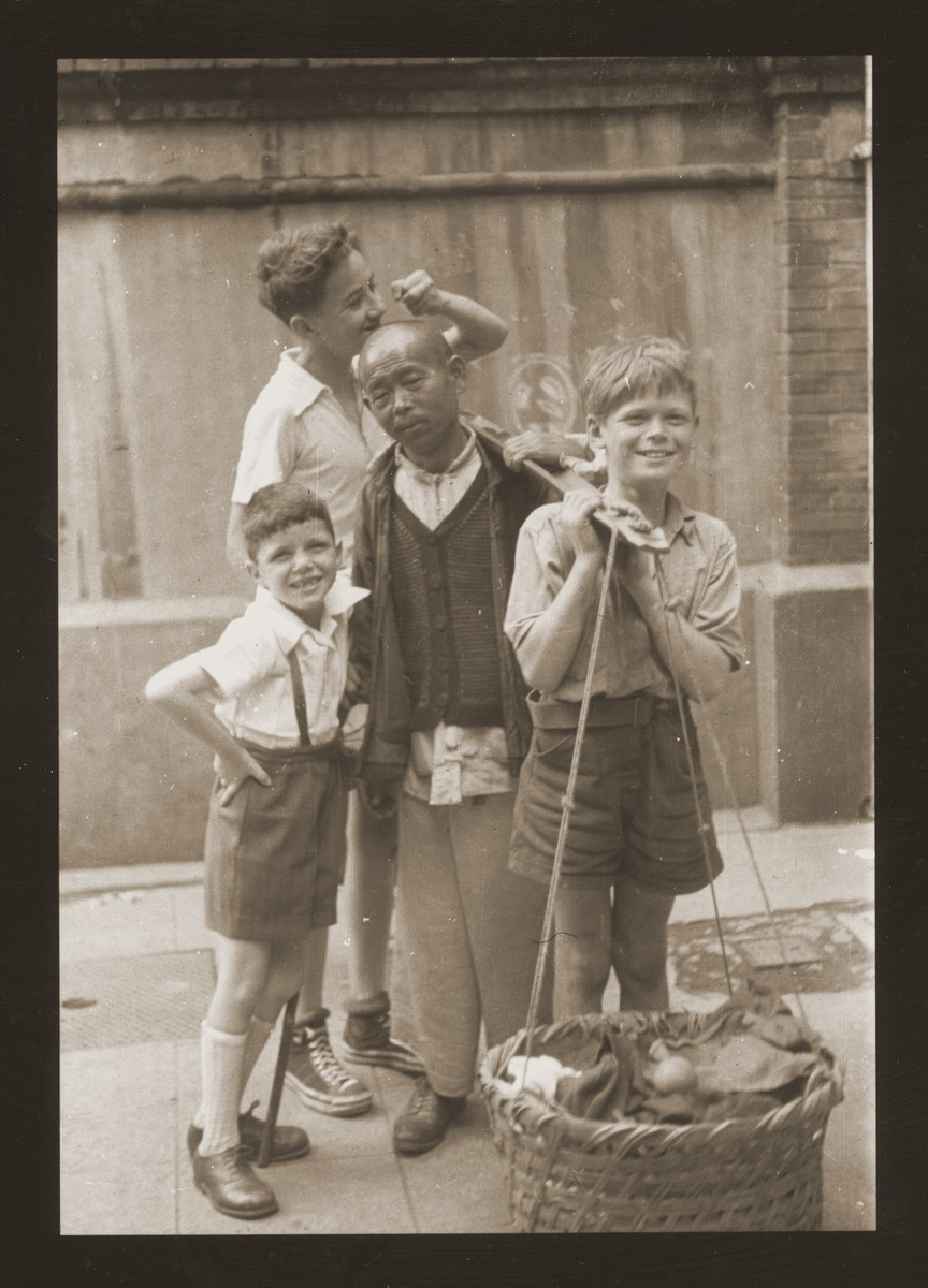 A Chinese street peddler stands with three Jewish refugee boys.  Harry Fiedler is on the far left.