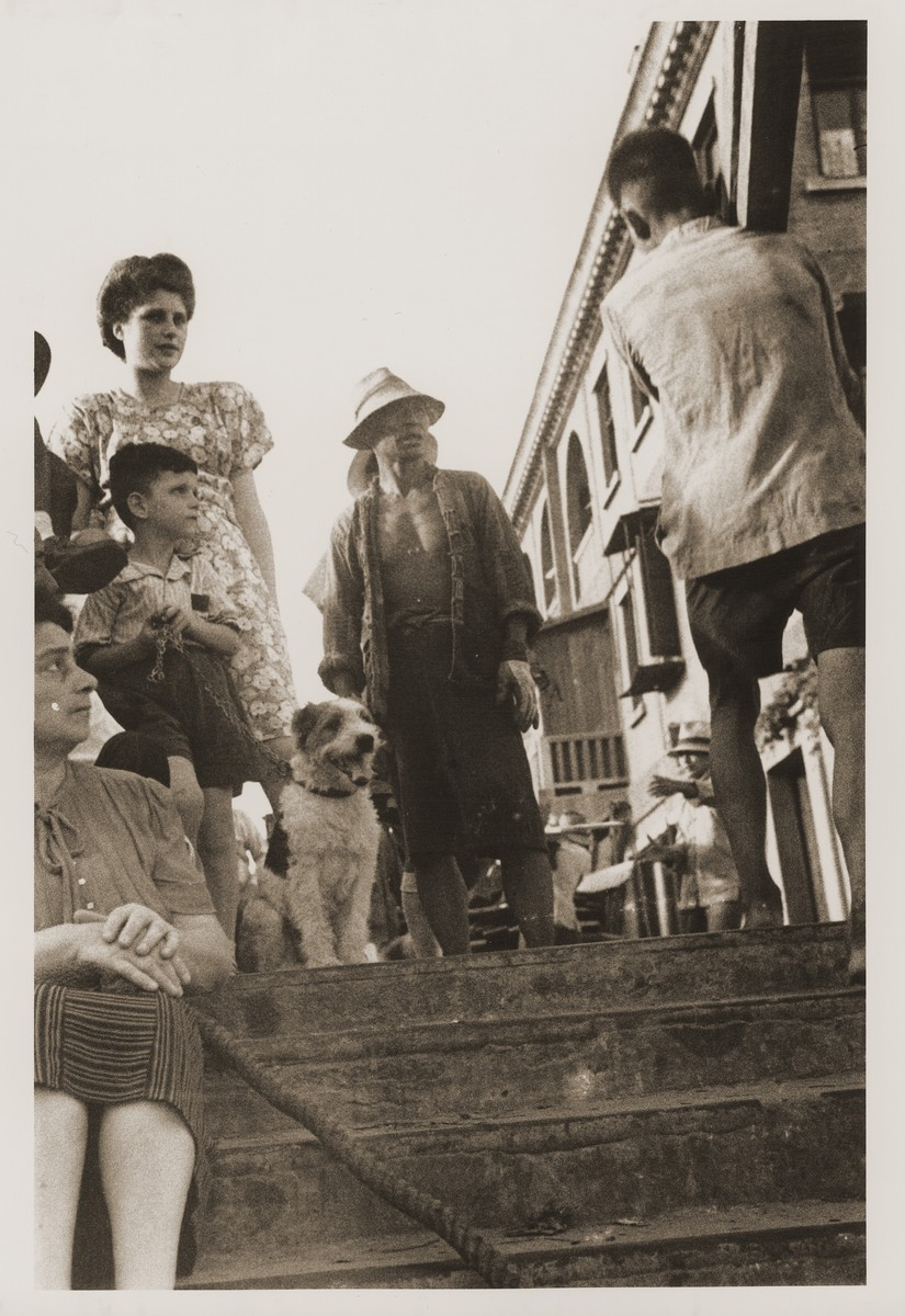 Jewish refugees on a street in the Hongkew district of Shanghai.  Pictured are Harry Fiedler, Julla and Camilla Goldstaub with their pet dog.