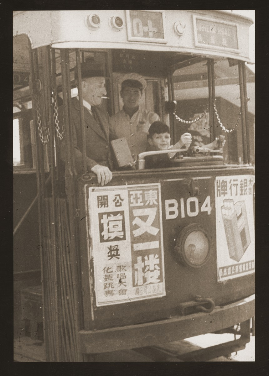 Harry Fiedler sits in the driver's seat of a Shanghai streetcar.  Pictured next to him, with a cigarette, is his uncle, Adolph Goldstaub.