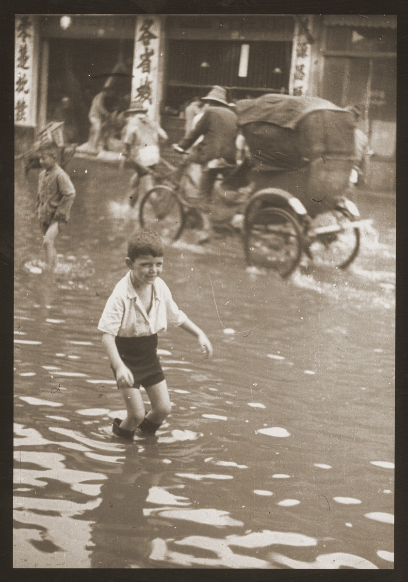 Harry Fiedler plays in the water of a flooded street [Tongshan Road] in Shanghai.  Behind him, a pedicab cuts through the water.